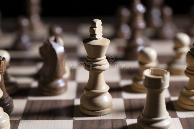 Chess game. White and black pieces are fighting for victory. The Central figure is in focus. The concept of teamwork royalty free stock image