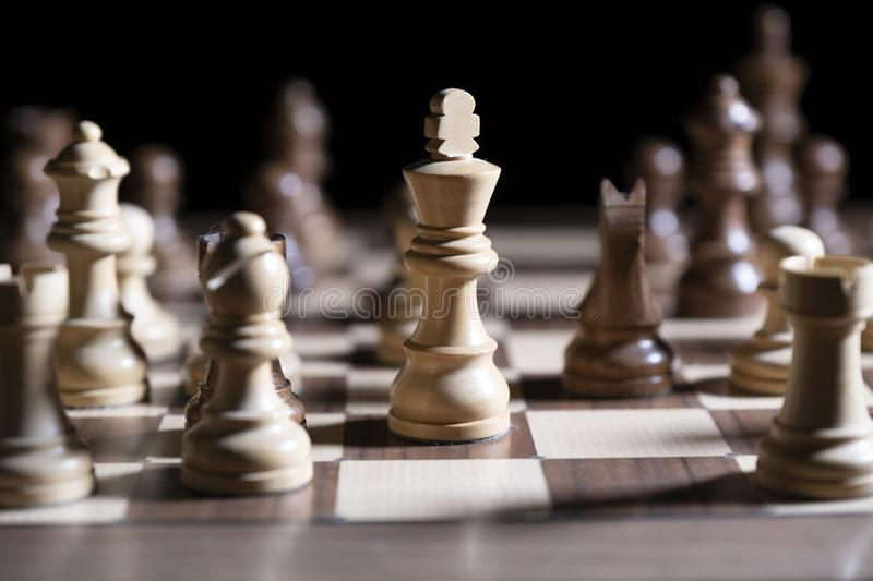 Chess game. White and black pieces are fighting for victory. The Central figure is in focus. The concept of teamwork royalty free stock photo