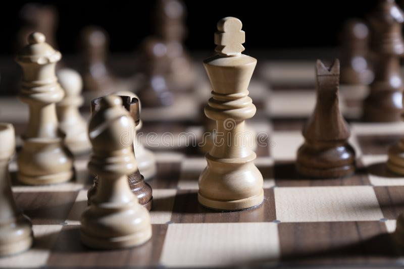 Chess game. White and black pieces are fighting for victory. The Central figure is in focus. The concept of teamwork royalty free stock photography
