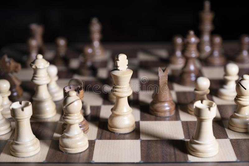 Chess game. White and black pieces are fighting for victory. The Central figure is in focus. The concept of teamwork stock photos