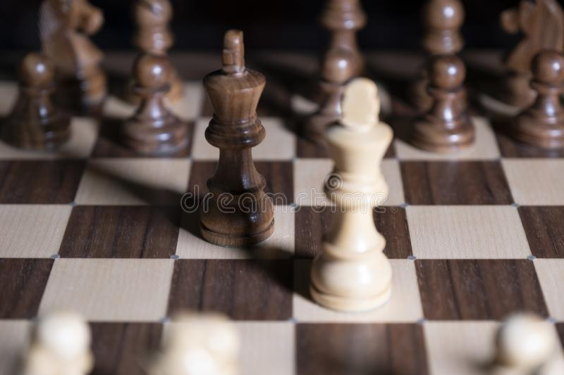 Chess game. White and black pieces are fighting for victory. The Central figure is in focus. The concept of teamwork stock image