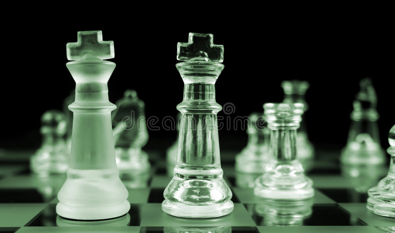 Chess - Heads Up. Glass Chess Pieces on a Frosted Glass Chess Board royalty free stock photos