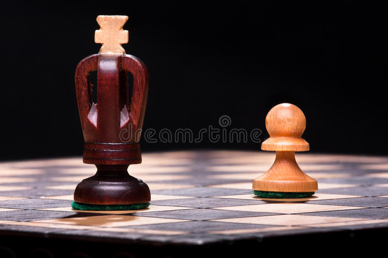 Chess king with pawn. On the wooden board stock photography