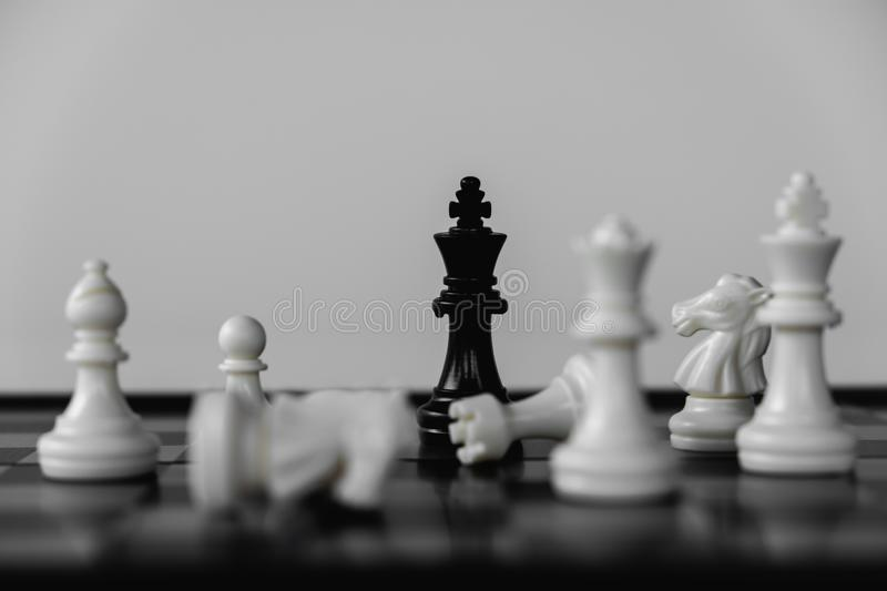 Chess King stand surrounded by enemies. The winner in business competition. Competitiveness and strategy. Leader, courage, success, brave, hero, power, strong royalty free stock photography