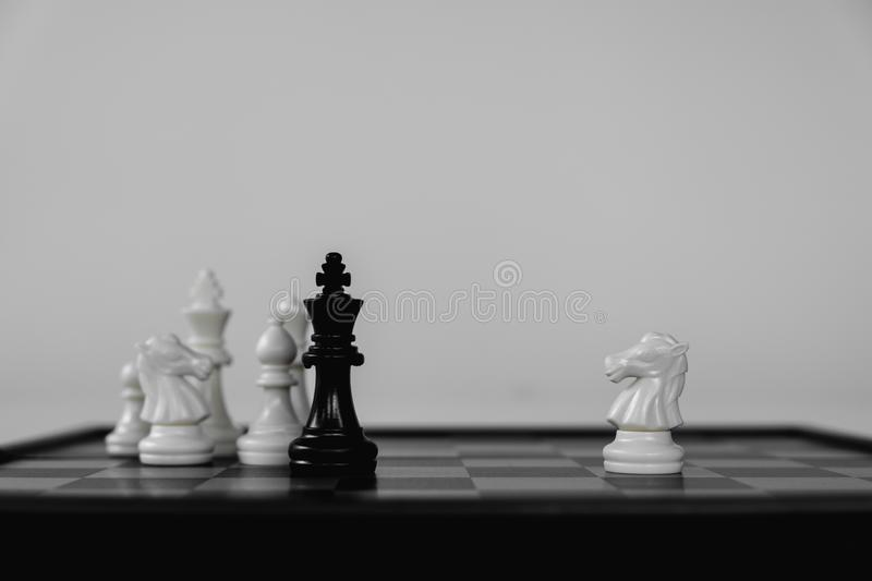 Chess King stand surrounded by enemies. The winner in business competition. Competitiveness and strategy. Leader, courage, success, brave, hero, power, strong stock images