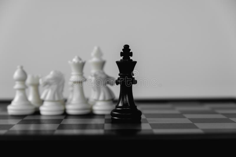 Chess King stand surrounded by enemies. The winner in business competition. Competitiveness and strategy. Leader, courage, success, brave, hero, power, strong stock image