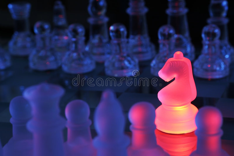 Chess Knight. Closeup shot of a chessboard with knight highlighted by red light stock photos