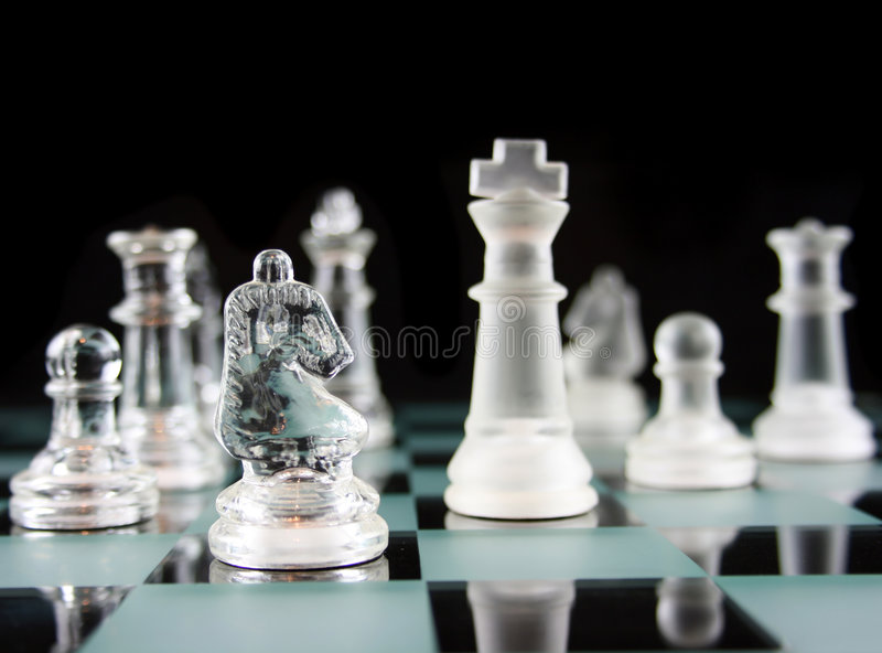 Chess - Knight Moves. Glass Chess Pieces on a Frosted Glass Chess Board royalty free stock photo