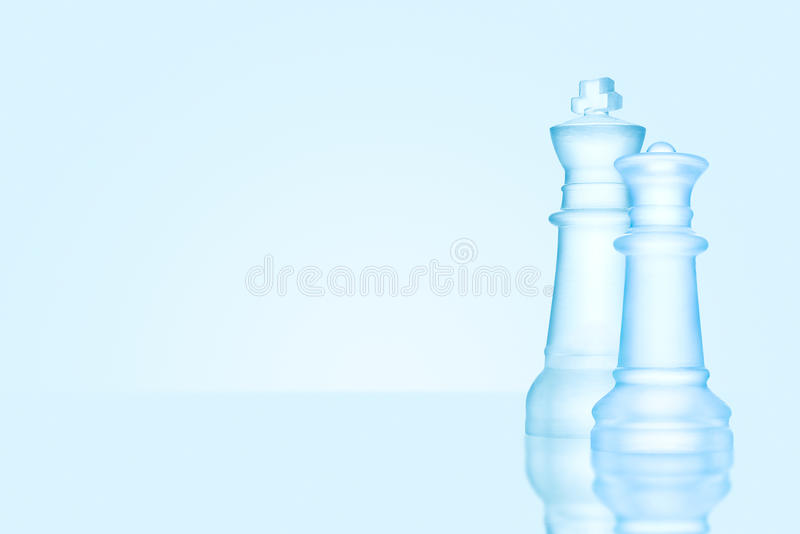 Chess leaders. Chess game concept of icy frosted king and queen, the most powerful figures standing together on glacial chessboard stock photo