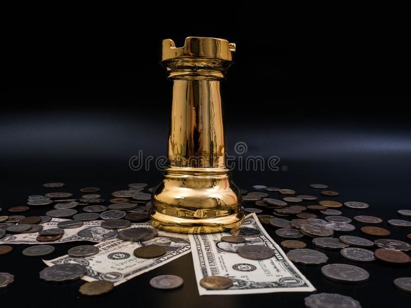 Chess leadership concept with gold on a pile of coins and banknotes isolated in black background. Chess concept save the strategy stock photos