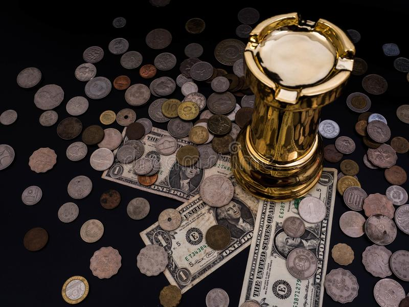 Chess leadership concept with gold on a pile of coins and banknotes isolated in black background. Chess concept save the strategy royalty free stock photography
