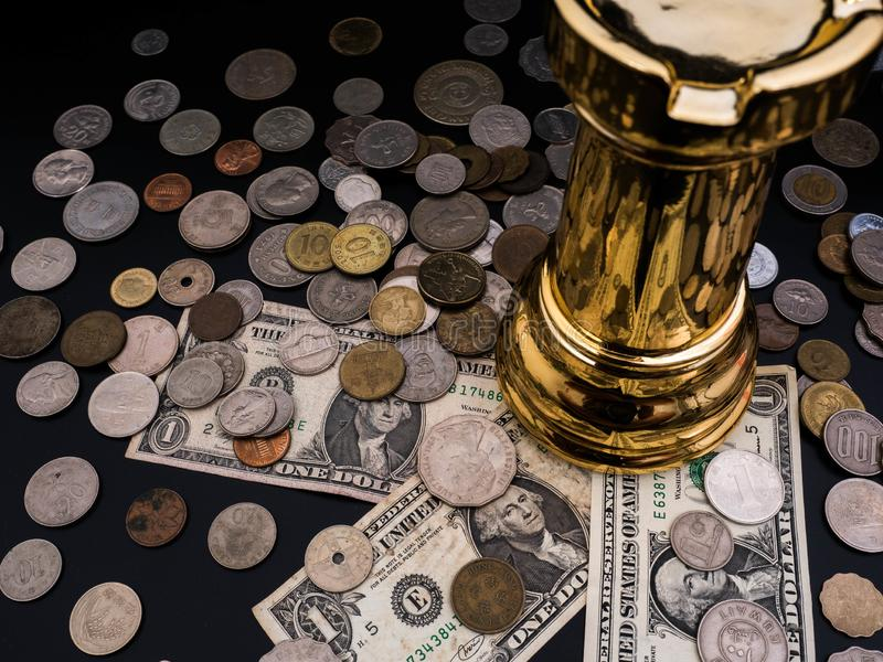Chess leadership concept with gold on a pile of coins and banknotes isolated in black background. Chess concept save the strategy royalty free stock image