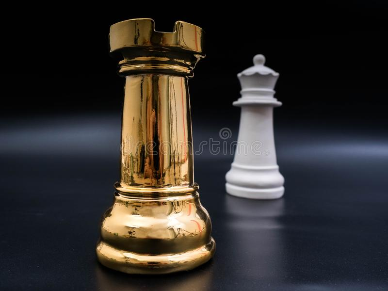 Chess leadership concept with gold and white chess isolated in black background. Chess concept save the strategy royalty free stock images