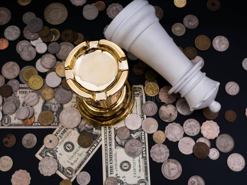 Chess leadership concept with gold and white chess on a pile of coins and banknotes isolated in black background. Chess concept stock photography
