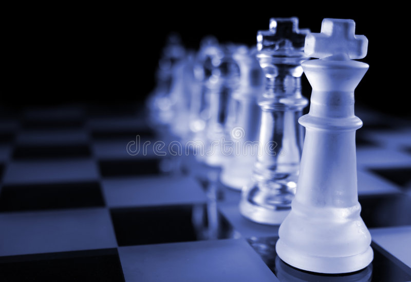 Chess - The Line Up. Glass Chess Pieces on a Frosted Glass Chess Board royalty free stock images