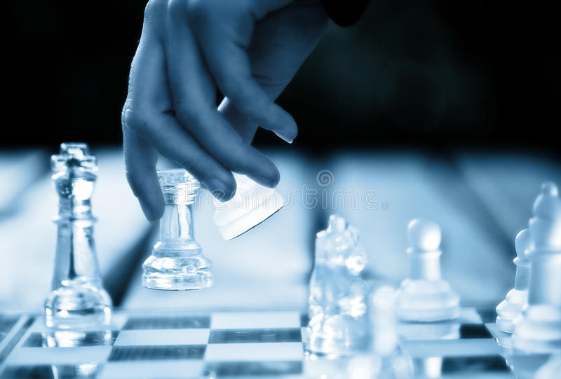 Chess move. Hand making a winning chess move royalty free stock photo