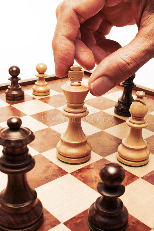 Chess Move Hand Business Strategy. A wood chessboard with a hand starting to move a pawn chess piece stock photo