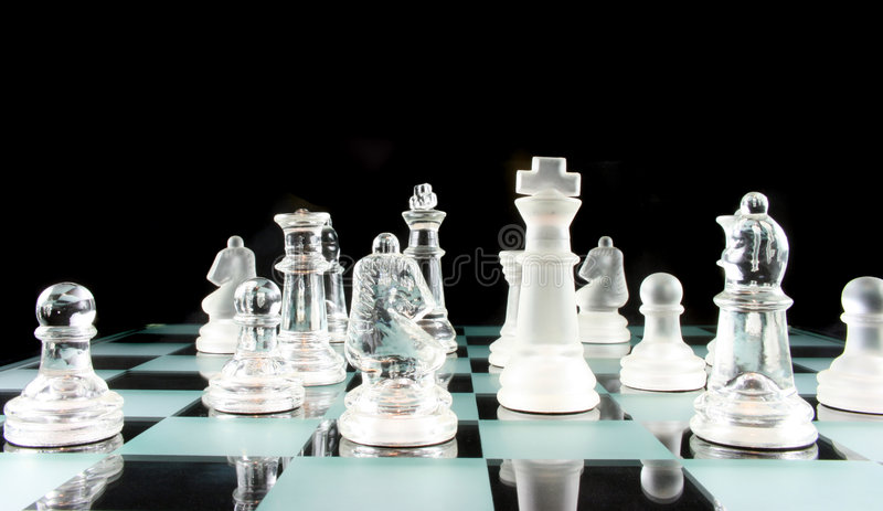 Chess - My Move I think. Glass Chess Pieces on a Frosted Glass Chess Board royalty free stock photography
