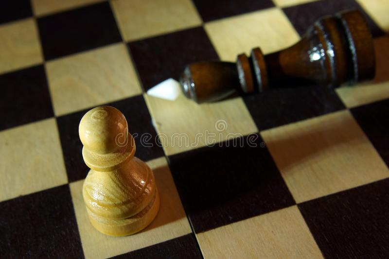 Chess pawn won opposite king. Victory in unequal fight stock photo