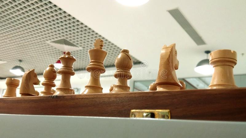 Chess piece on chess board with ceiling decoration background. stock photos