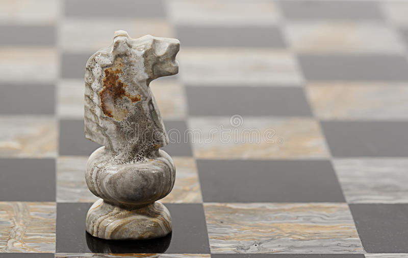 Chess Piece Knight. An onyx Knight chess piece on black and multi colored onyx chess board royalty free stock photos