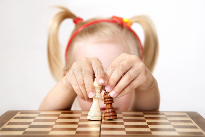 Chess pieces. She plays with chess pieces royalty free stock photo