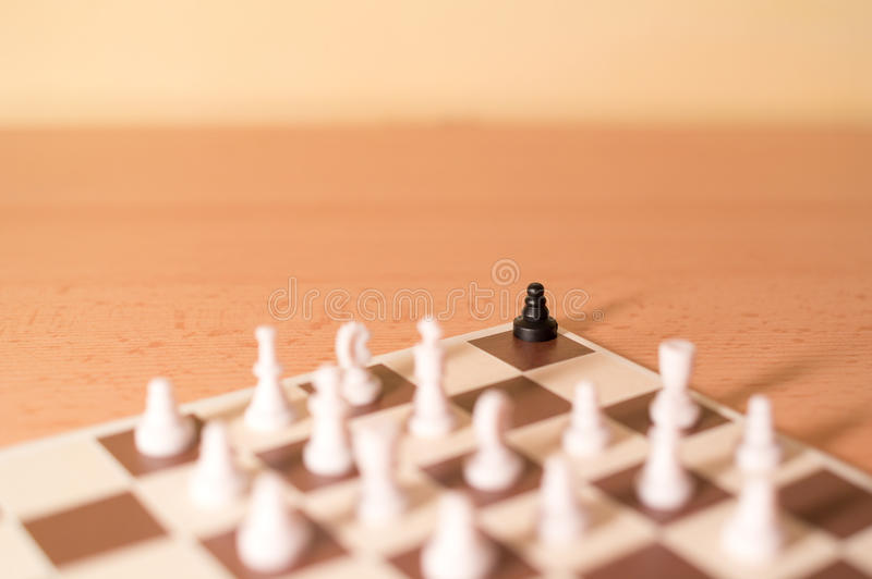 Chess pieces as metaphor - racism and bullying. One black piece is in the corner surrounded by big majority of white pieces stock photos