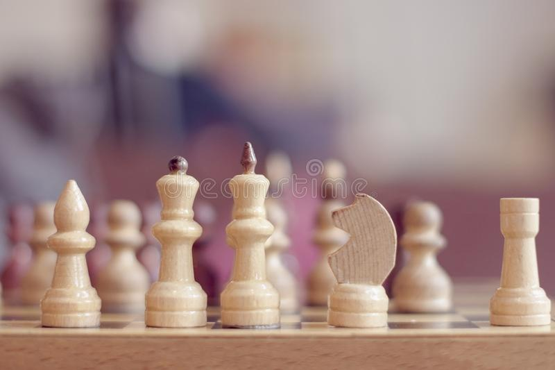Chess pieces on the board in blur. Selective focus royalty free stock image