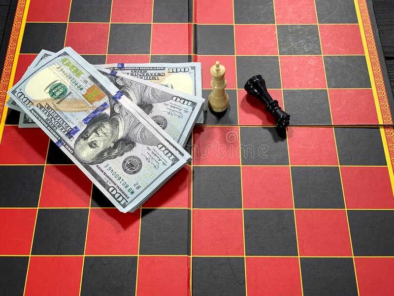 Chess pieces on the board, game for money. Financial disputes. Red and black checkered boards. A pack of dollars royalty free stock image