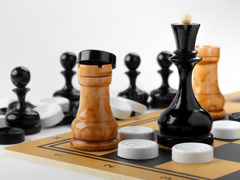 The chess pieces and checkers placed on the chessboard. White background royalty free stock photography