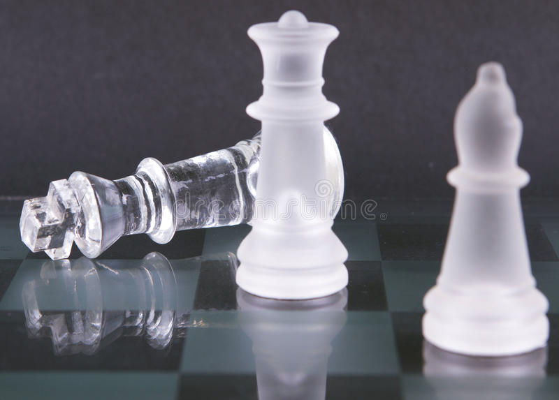 Chess pieces checkmate. A collection of glass chess pieces end game checkmate royalty free stock photo