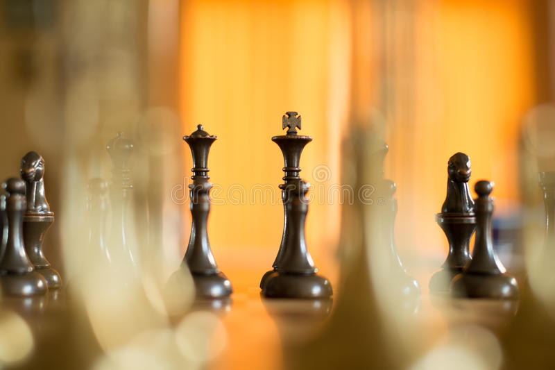 Chess Pieces on a Chess Board. Macro showing the King, Queen and Bishop and pawn in a chess game. The Opposing Players Pieces are in the Background. The game is royalty free stock photo