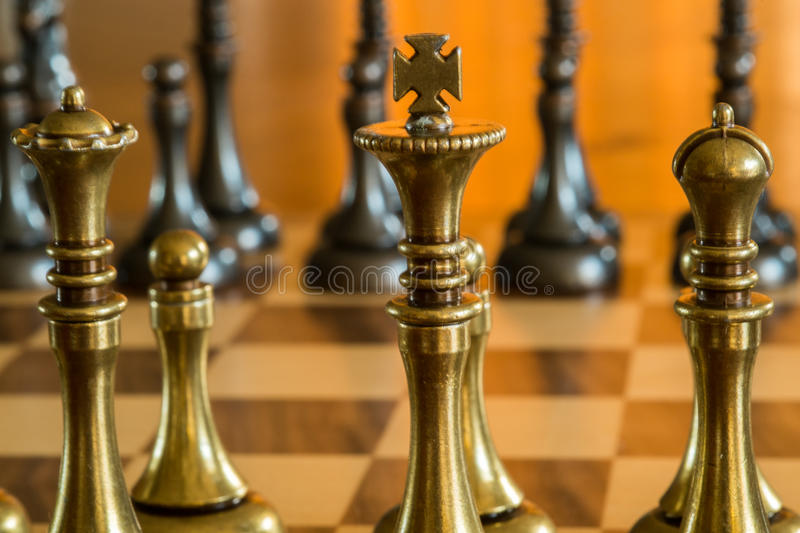 Chess Pieces on a Chess Board. Macro showing the King, Queen and Bishop and pawn in a chess game. The Opposing Players Pieces are in the Background. The game is stock photo