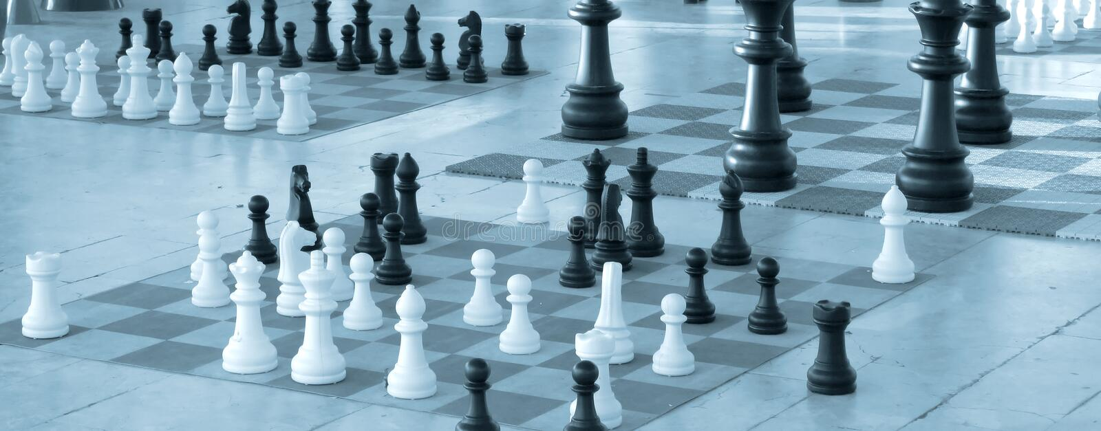 Chess pieces in diferent sizes - Blue tint. Chess pieces in diferent size on a chess boards - Blue tint stock photo