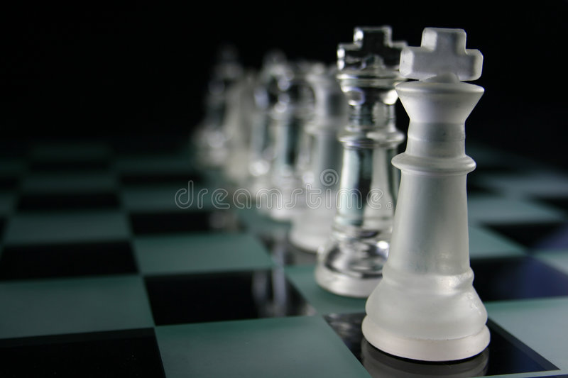 Chess Pieces fading. Chess Game - Chess Pieces on a glass chessboard stock photos