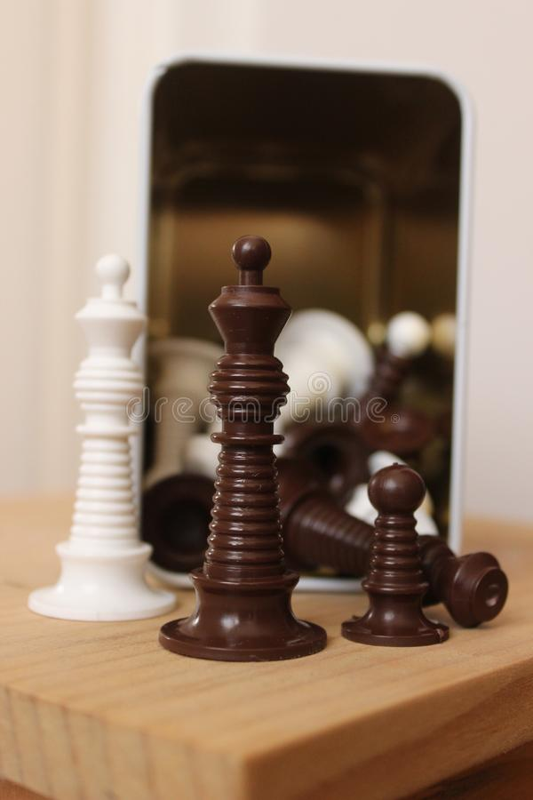 Chess pieces in front of a metal container stock photo