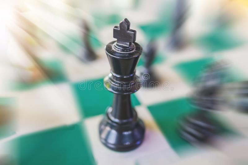 Chess pieces on the green board blury background. Chess pieces on the green board blur background stock photos