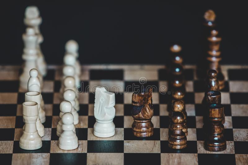 Chess pieces knights facing each other for a standoff on chessboard with blurred background. Chess knights confronting each other royalty free stock images