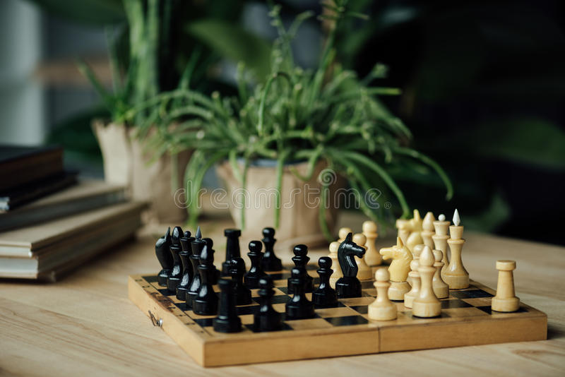 Chess pieces knights standing head to head on chessboard on the table royalty free stock photo