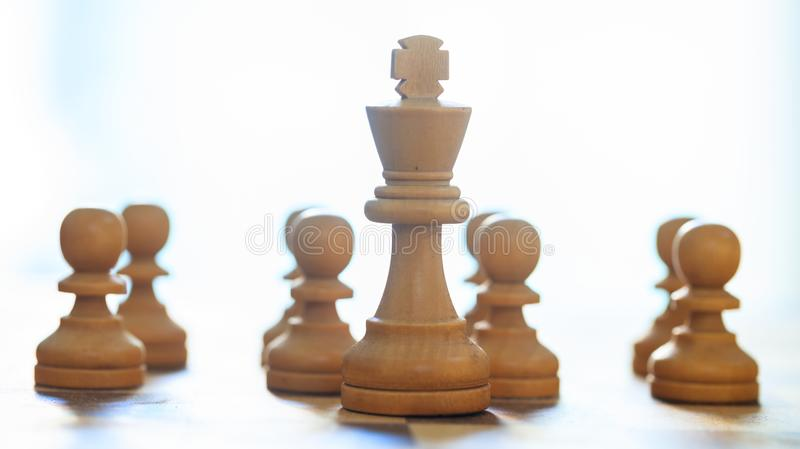 Chess pieces light brown color. Close up view of king and pawns with details. Blurred background. stock images