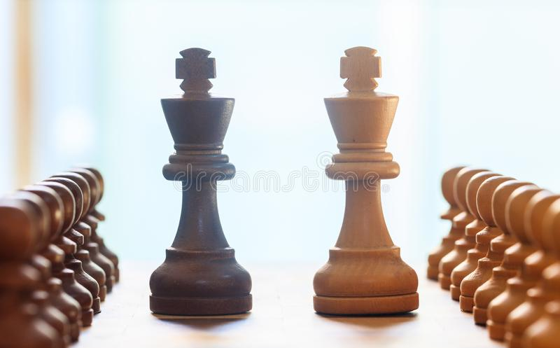 Chess pieces light, dark brown color. Close up view of kings and pawns with detail. Blur background. stock photo