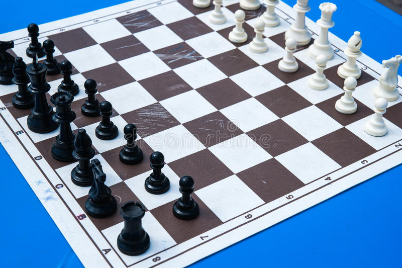 Chess pieces on a paper chess board. Black and white plastic chess pieces on a cheap and used paper chess board on a blue table. Open air chess competitions royalty free stock photos