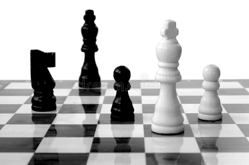 Chess pieces, white king under attack stock images