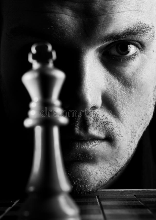 The chess player. Low key portrait of man playing chess royalty free stock photo