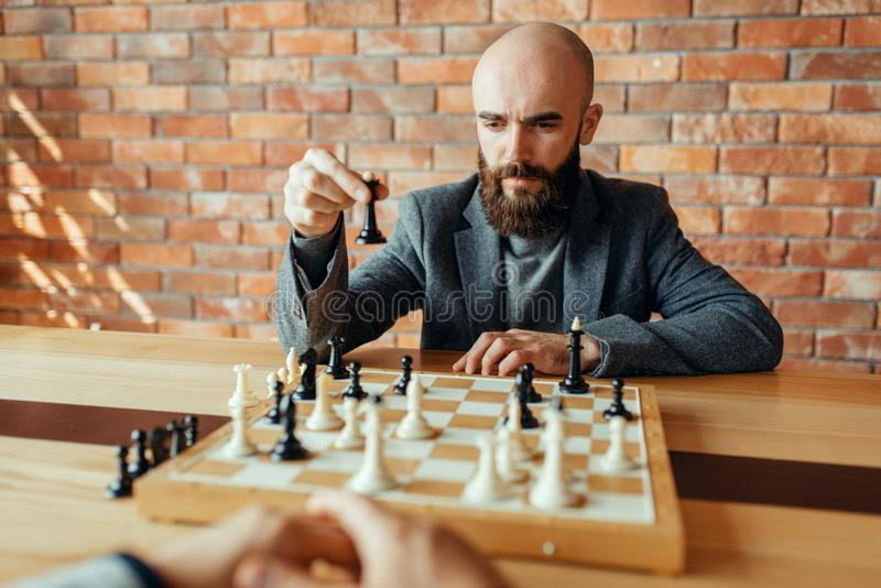 Chess player playing black figures, queen move royalty free stock photos
