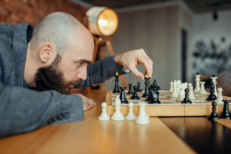 Chess player playing black figures, queen move royalty free stock photo