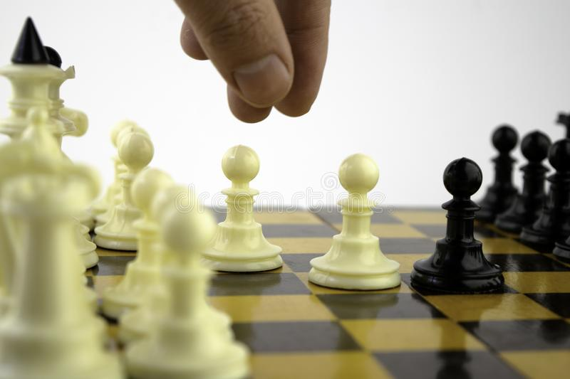The chess player`s hand moves the pawn on a board during the game of chess. The chess player`s hand moves the pawn on the board during the game of chess stock photos