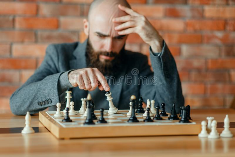Chess player understood that he lost, checkmate. Male chess player understood that he lost, checkmate. Chessplayer at board, front view, intellectual tournament stock photo