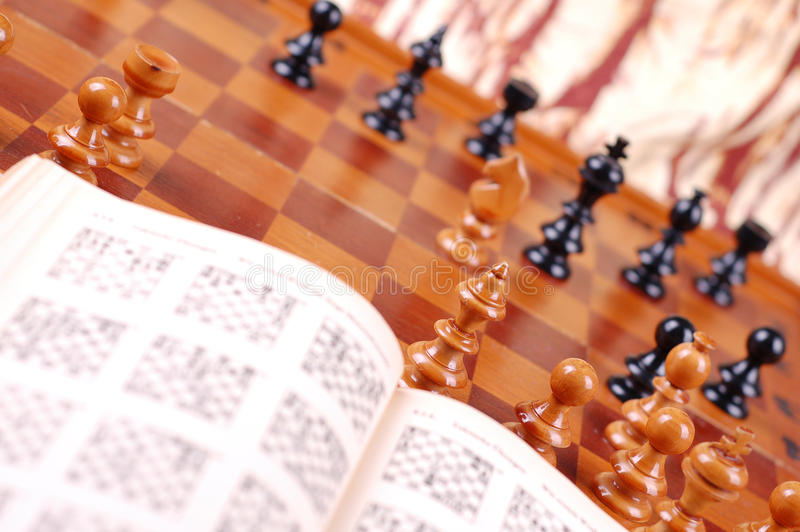 Chess table and open book. Chess table with chess pieces and an open book. Suggest studying chess strategy. the chess pieces closer to the camera are in focus royalty free stock photography