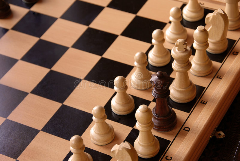 Chessboard. With black queen among white figures stock image